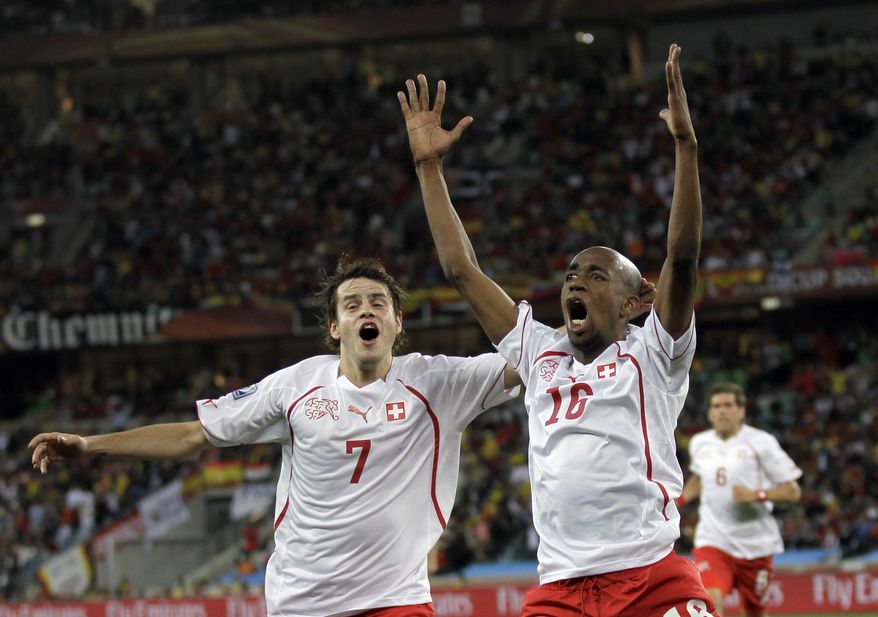 Switzerland's Gelson Fernandes, right, celebrates with his teammate Tranquillo Barnetta after scoring during the World Cup group H soccer match between Spain and Switzerland at the stadium in Durban, South Africa on Wednesday, June 16, 2010. (AP Photo/Julie Jacobson)