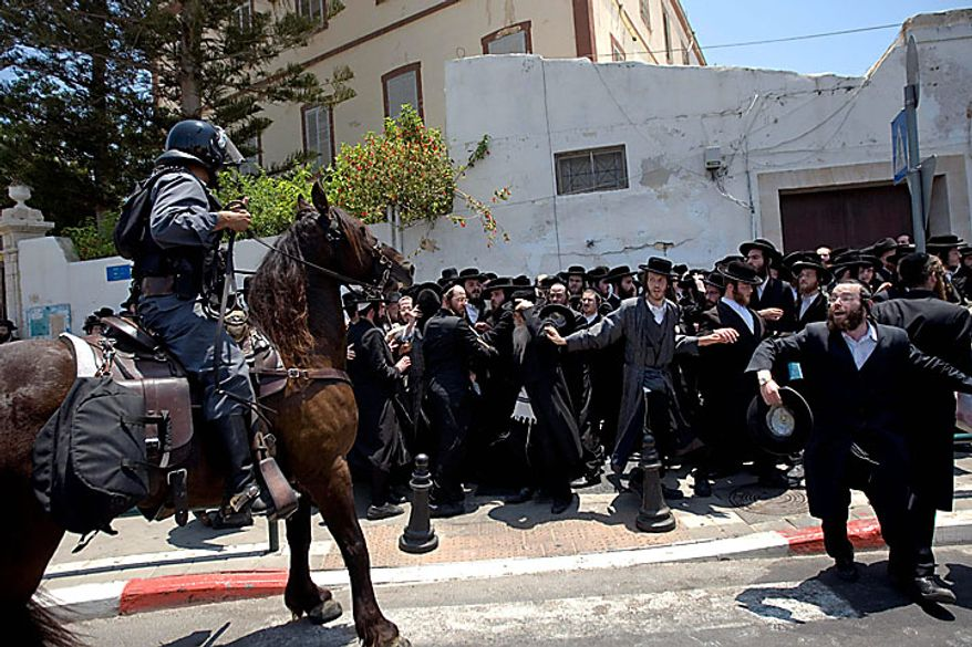 Ultra-Orthodox Jewish men scuffle with mounted police officers during a protest against the removal of ancient tombs in the neighborhood of Jaffa, Tel Aviv, Israel on Wednesday, June 16, 2010. Israeli police say they have arrested several dozen people in a violent protest by ultra-Orthodox activists opposed to an excavation they say is disturbing Jewish gravesites. Five police officers and 10 demonstrators were slightly wounded. (AP Photo/Ariel Schalit)