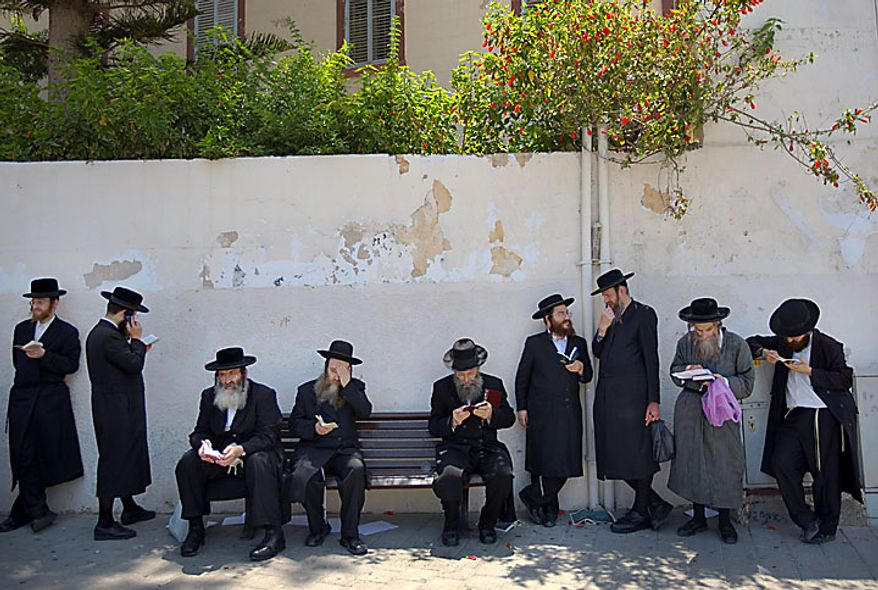 Ultra-Orthodox Jewish men pause during a protest against the removal of ancient tombs in the neighborhood of Jaffa, Tel Aviv, Israel on Wednesday, June 16, 2010.  Israeli police say they have arrested several dozen people in a violent protest by ultra-Orthodox activists opposed to an excavation they say is disturbing Jewish gravesites. Five police officers and 10 demonstrators were slightly wounded. (AP Photo/Ariel Schalit)