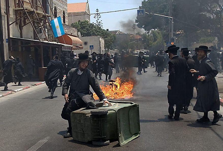 Ultra-Orthodox Jewish men run during a protest against the removal of ancient tombs in the neighborhood of Jaffa, Tel Aviv, Israel, Wednesday, June 16, 2010. Israeli police say they have arrested several dozen people in a violent protest by ultra-Orthodox activists opposed to an excavation they say is disturbing Jewish grave sites. Five police officers and ten demonstrators were lightly wounded. (AP Photo/Ariel Schalit)