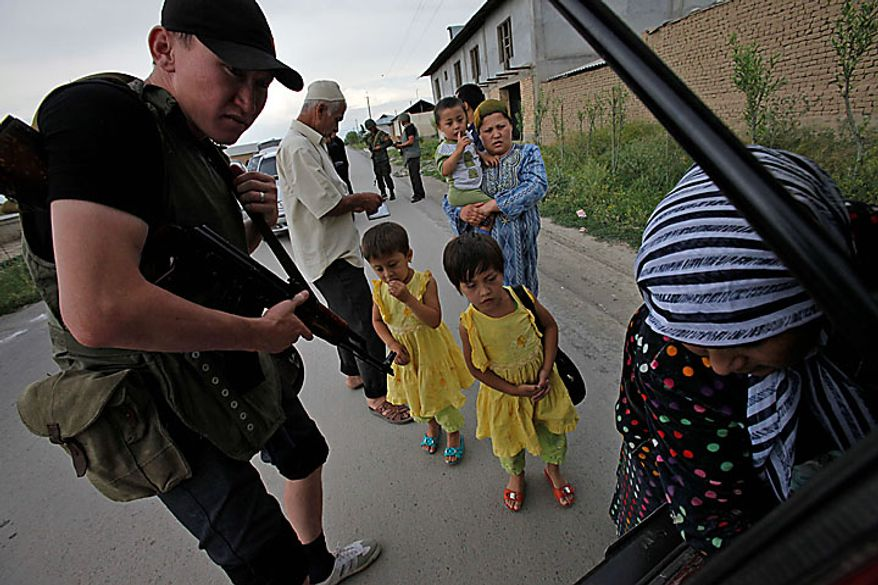 A Kyrgyz Army volunteer checks the trunk of passing car during a search for weapons as an ethnic Uzbek family look on at a checkpoint on the Uzbek side of the border near Osh, Kyrgyzstan, on Wednesday, June 16, 2010. Heavy arms fire rang out over Osh before dawn Wednesday as authorities struggled to bring order to the country's south, which has been thrust into chaos by days of deadly ethnic riots. The violence has prompted more than 100,000 Uzbeks to flee for their lives to Uzbekistan, with tens of thousands more camped on the Kyrgyz side or stranded in a no man's land. (AP Photo/Alexander Zemlianichenko)