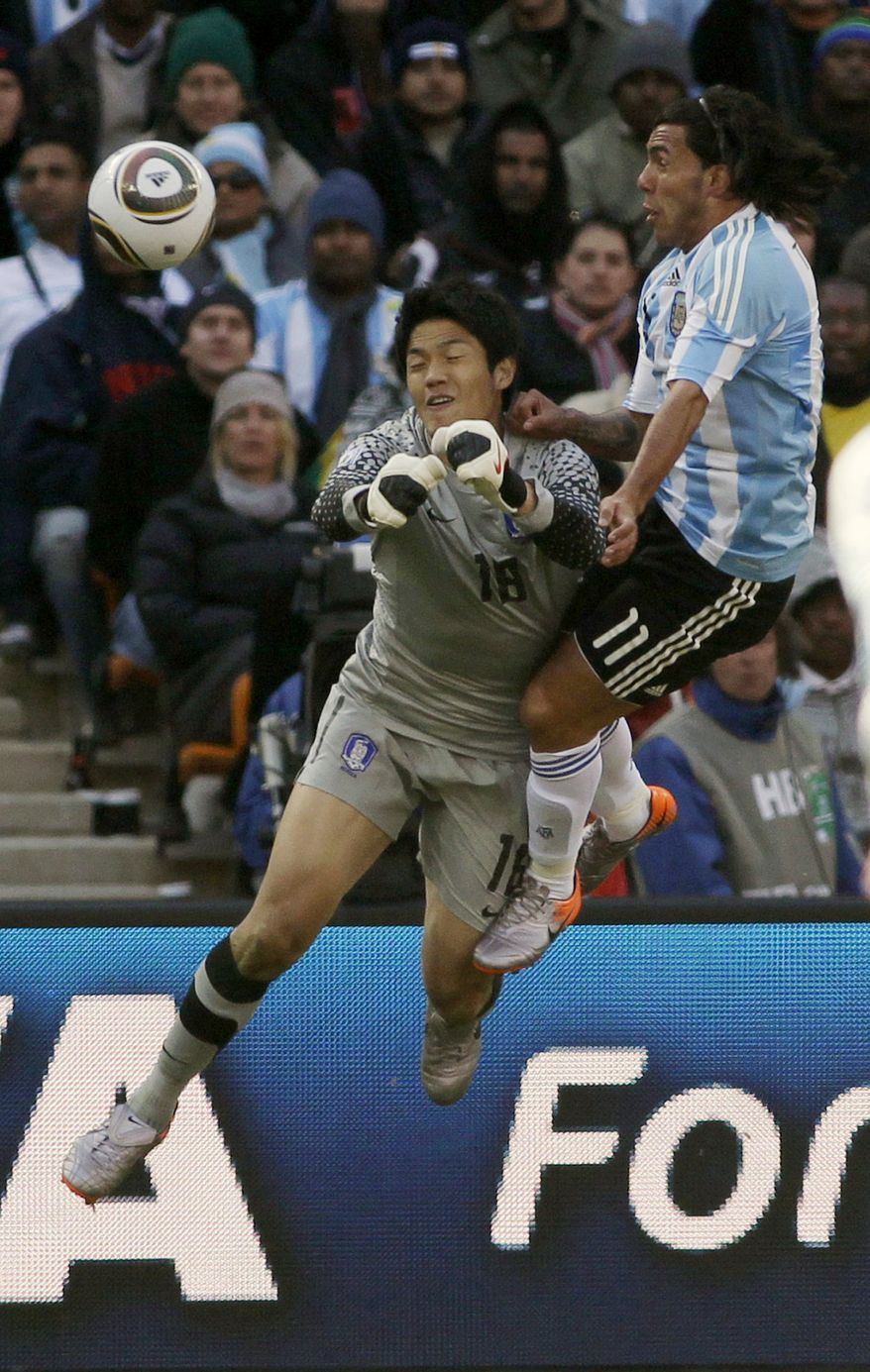 South Korea goalkeeper Jung Sung-Ryong, left, punches the ball away from Argentina's Carlos Tevez, right, during the World Cup group B soccer match between Argentina and South Korea at Soccer City in Johannesburg, South Africa, Thursday, June 17, 2010. (AP Photo/Ivan Sekretarev)
