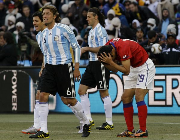 South Korea's Ki Sung-Yong, right, reacts after missing a chance to score during the World Cup Group B soccer match between Argentina and South Korea at Soccer City in Johannesburg, South Africa, Thursday, June 17, 2010. Second left is Argentina's Gabriel Heinze. (AP Photo/Frank Augstein)