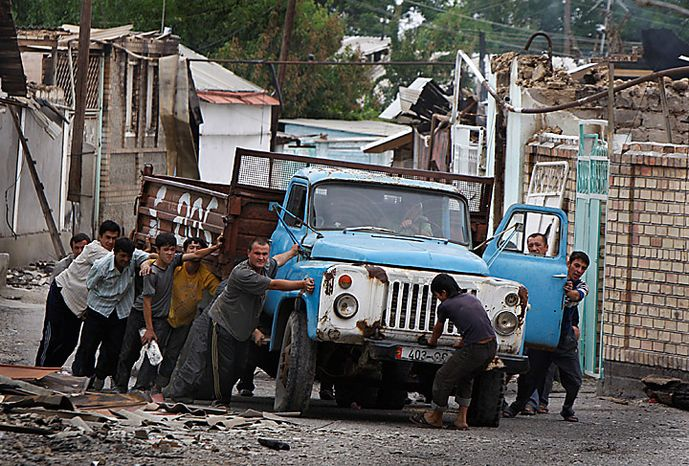 Uzbek men push a truck as they build a barricade in the Uzbek district in the southern Kyrgyz city of Osh on Thursday, June 17, 2010.  Some 400,000 people have been displaced by ethnic violence in southern Kyrgyzstan, the United Nations announced Thursday, dramatically increasing the official estimate of a refugee crisis that has left throngs of desperate, fearful people without enough food and water in grim camps along the Uzbek border. (AP Photo/Sergei Grits)