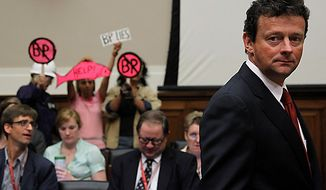 Protestors stand behind BP CEO Tony Hayward as he arrives on Capitol Hill in Washington on Thursday, June 17, 2010, to testify before the House Oversight and Investigations subcommittee on the role of BP in the Deepwater Horizon explosion and oil spill. (AP Photo/Haraz N. Ghanbari)