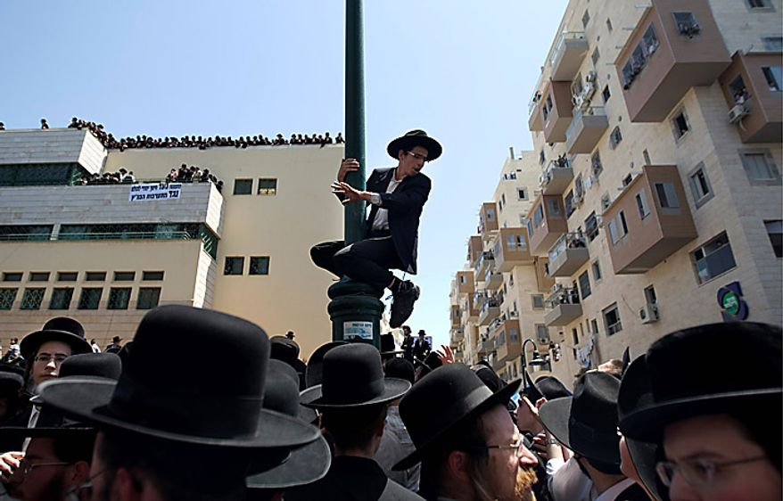 An Ultra-Orthodox Jewish man climbs on a pole in Bnei Brak, Israel, on Thursday, June 17, 2010, during a demonstration against an Israeli Supreme Court ruling forcing the integration of a religious girls school. Tens of thousands demonstrated in Bnei Brak, and an even bigger protest took place in Jerusalem. (AP Photo/Ariel Schalit)