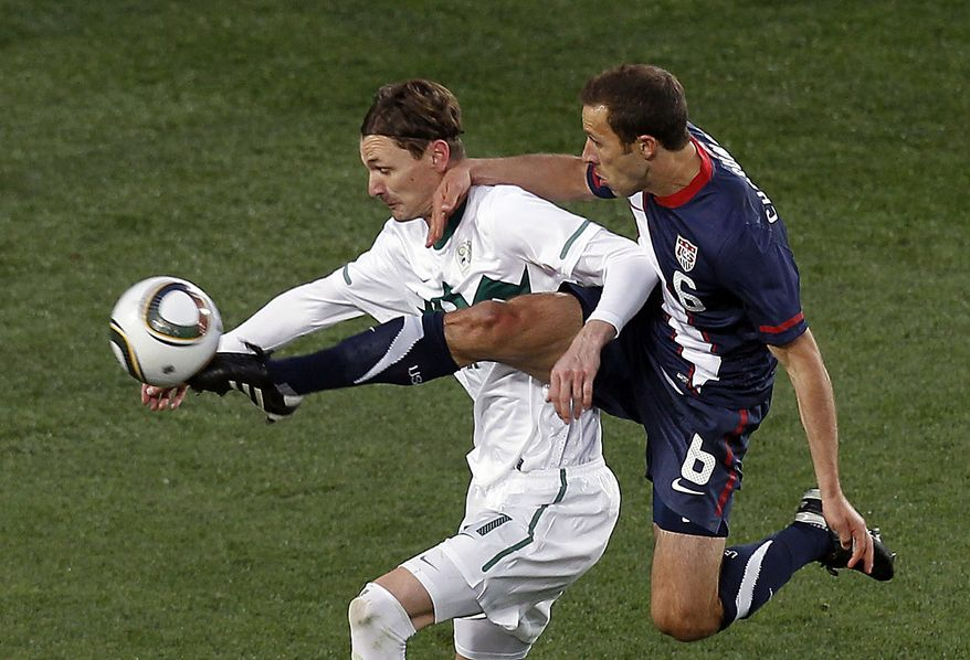 Slovenia's Milivoje Novakovic, left, and the United States' Steve Cherundolo, right, compete for the ball during the World Cup group C soccer match between Slovenia and the United States at Ellis Park Stadium in Johannesburg, South Africa, Friday, June 18, 2010.  (AP Photo/Hassan Ammar)