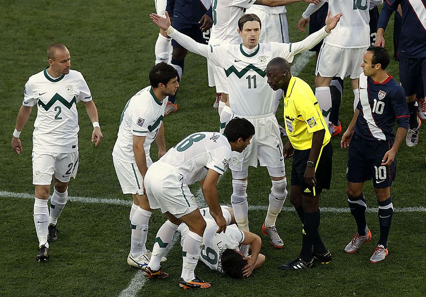 Slovenia's Milivoje Novakovic, center, remonstrates with referee Koman Coulibaly of Mali, second from right, after Slovenia's Zlatan Ljubijankic, bottom, collided with United States' Clint Dempsey, not seen, during the World Cup group C soccer match between Slovenia and the United States at Ellis Park Stadium in Johannesburg, South Africa, Friday, June 18, 2010.  (AP Photo/Hassan Ammar)