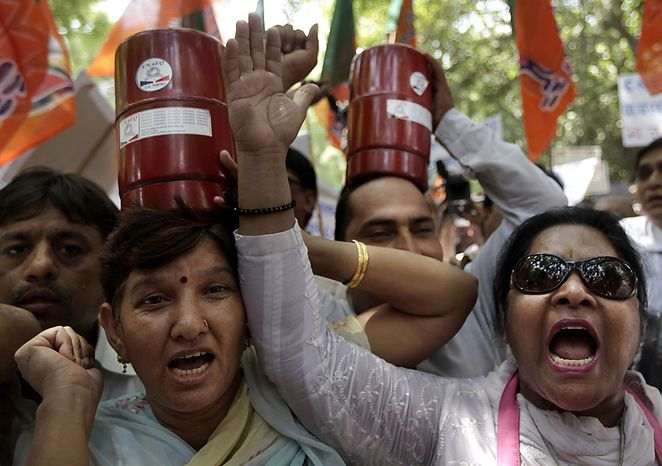 Supporters of India's main opposition Bharatiya Janata Party carry gas cylinders as they protest rise in price of essential commodities and fuel in capital New Delhi on Friday, June 18, 2010. (AP Photo/Saurabh Das)