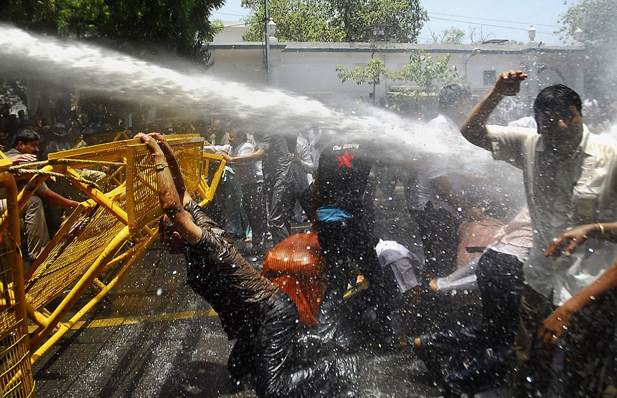 Supporters of India's main opposition Bharatiya Janata Party face a water-canon burst as they protest rise in price of essential commodities and fuel in capital New Delhi on Friday, June 18, 2010. (AP Photo)