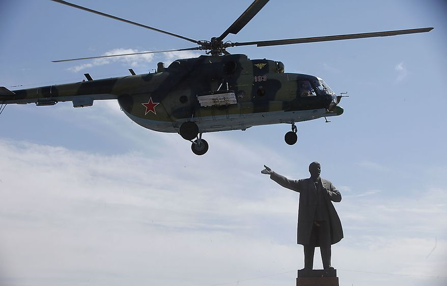 A military helicopter with Kyrgyzstan's interim President Rosa Otunbayeva on board flies over the statue of of the Soviet founder Vladimir Lenin prepares to land on the central square in the southern Kyrgyz city of Osh, Kyrgyzstan, Friday, June 18, 2010. Ms. Otunbayeva is vowing to work for the return of refugees who fled deadly ethnic violence there by the hundreds of thousands. (AP Photo/Alexander Zemlianichenko)