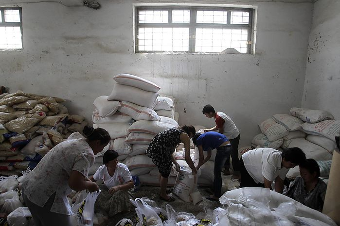Charity society volunteers pack food in Jalal-Abad, Kyrgyzstan, Friday, June 18, 2010. Some 400,000 people have been displaced by ethnic violence in southern Kyrgyzstan, the United Nations announced Thursday, dramatically increasing the official estimate of a crisis that has left throngs of desperate, fearful refugees without enough food and water in grim camps along the Uzbek border. (AP Photo/Sergey Ponomarev)