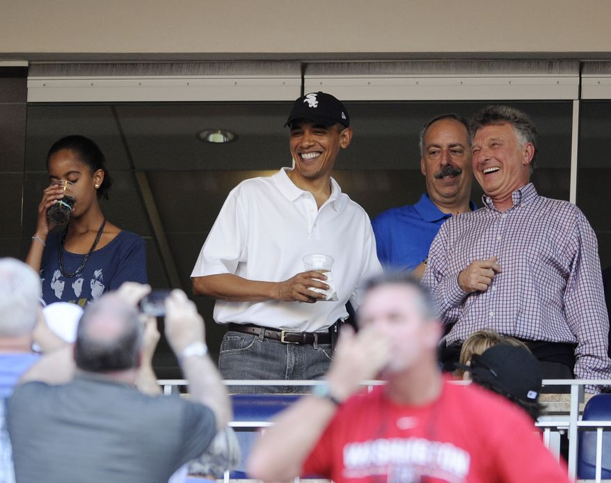 President Barack Obama, wearing a White Sox baseball cap, attends a baseball game between the Washington Nationals and the Chicago White Sox, Friday, June 18, 2010, in Washington. His daughter Malia is at left. (AP Photo/Nick Wass)