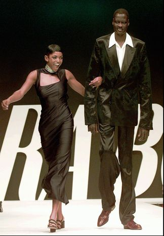 FILE - In this Oct. 2, 1996 photo, Keba Phipps, left, former player of the US volleyball Olympic team, and Manute Bol, of Sudan, who played in NBA as center with Philadelphia 76ers, on the catwalk for Chiara Boni, at the unveiling of her collection for the Spring-Summer 1997 in Milan.