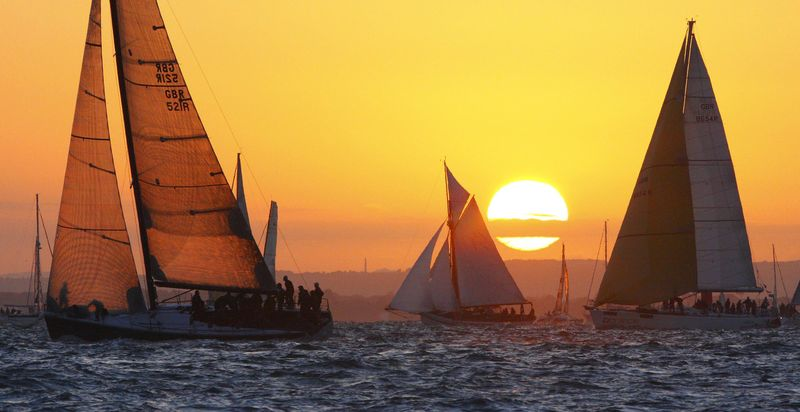 """The sun rises before the 5am start during the JP Morgan Asset Management Round the Island Race, with The yacht """"Bob"""" owned by BP Chief Executive Tony Hayward, left, Saturday June 19, 2010, near Cowes, Isle of Wight, off the south coast of England. Spokeswoman Sheila Williams said Hayward took time off his duties handling the environmental catastrophe in the Gulf of Mexico to see his boat participate in Saturday's race. (AP Photo/Chris Ison, PA)"""