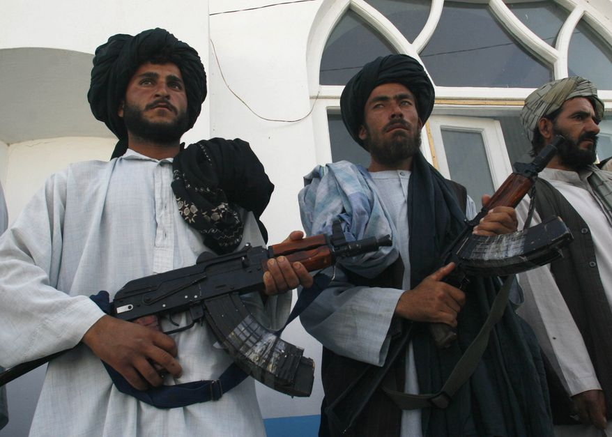 Former Taliban fighters stand in line as they surrender their weapons to Afghan authorities in Herat, west of Kabul, Afghanistan, on Saturday, June 19, 2010. (AP Photo/Reza Shirmohammadi)