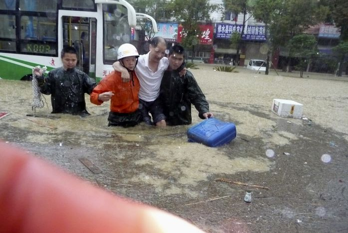 Chinese firemen evacuate a man trapped in the floods in Xiushui, in central China's Jiangxi province, on Sunday, June 20, 2010. Major rivers burst their banks in southern China, triggering massive floods that forced 860,000 to flee their homes, the government said Sunday. (AP Photo)