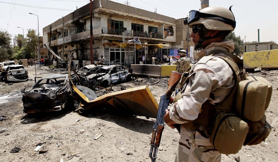 An Iraqi army soldier stands guard at the site of a car bombing in Baghdad on Sunday, June 20, 2010. Twin car bombs exploded Sunday near a major square in the Iraqi capital, killing at least 28 people and wounding dozens in the latest attack targeting a high-profile area in the capital. (AP Photo/Hadi Mizban)