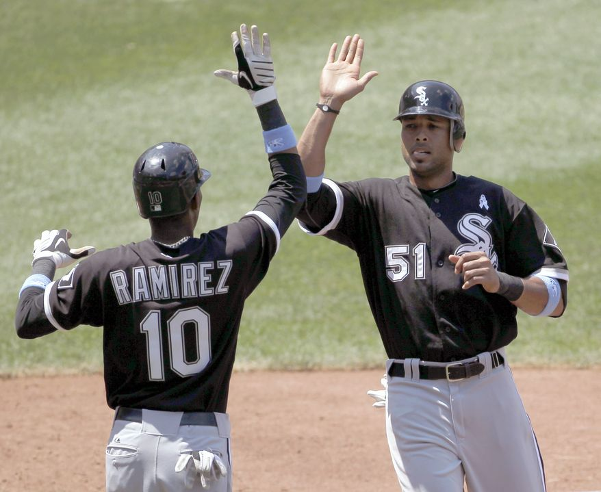 ASSOCIATED PRESS Chicago White Sox's Alexei Ramirez (10) and Alex Rios (51) celebrate after they scored on a single hit by teammate Paul Konerko against the Washington Nationals during the fifth inning of an interleague baseball game, Sunday, June 20, 2010, in Washington.