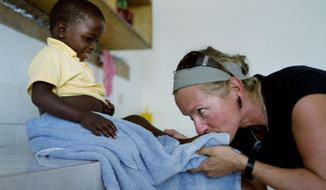 Canadian volunteer aid worker Tamara Palinka plays with Sonson at an orphanage on the outskirts of Port-au-Prince. Miss Palinka, 37, has sought unsuccessfully to adopt Sonson. (Associated Press)