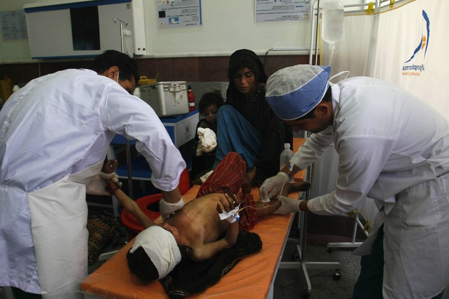 Medics treat a wounded Afghan boy in a hospital in Herat after he was injured in a clash between the police and Taliban in Afghanistan's Badghis province, Sunday, June 20, 2010. Three Taliban militants were killed and 33 others were wounded in the clash with police Sunday morning, according to Sharafudin Najebi, a Badghis province governor spokesman said. (AP Photo/Reza Shirmohammadi)