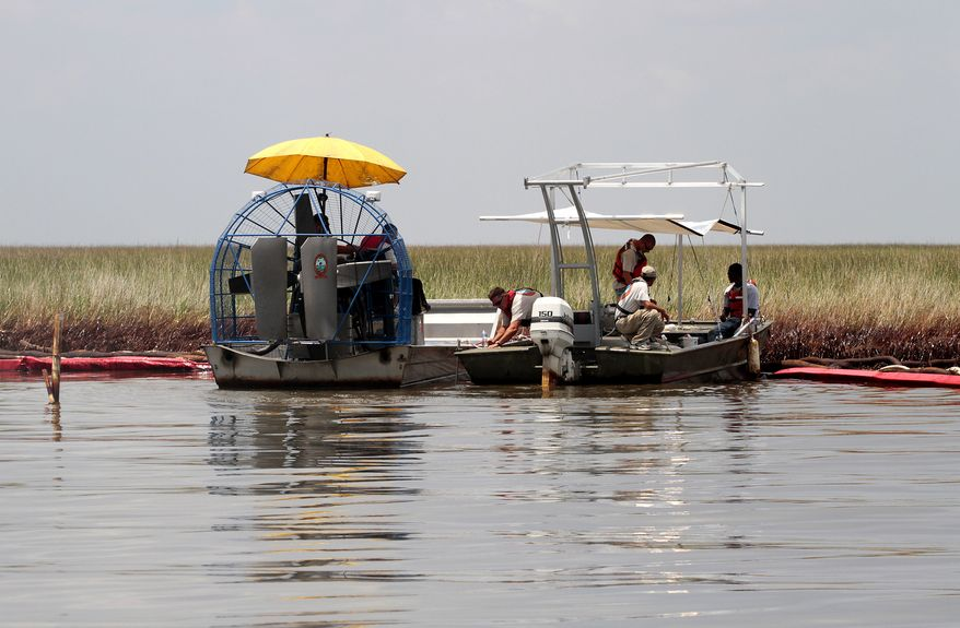 Workers vacuum up oil that has collected on marsh grass in Barataria Bay on the coast of Louisiana on Sunday, June 20, 2010. (AP Photo/Patrick Semansky)