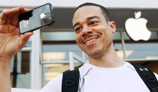"Thomas Smith, 32, of Boston, tries out the video on his new iPhone after standing in line outside the Apple Store in the Georgetown neighborhood of Washington, on Thursday, June 24, 2010. ""This is going to be the talk of the office today,"" says Smith. (AP Photo/Jacquelyn Martin)"