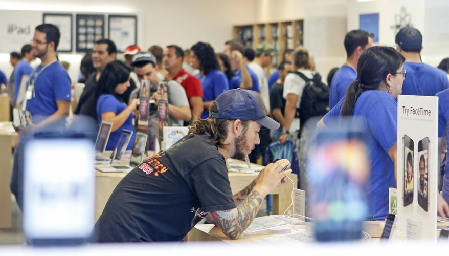 Fabricio Lioncio, foreground, of Miami Beach, checks out a new Apple iPhone 4 at the Apple store in Miami Beach, Fla., Thursday, June 24, 2010. Apple Inc.'s newest iPhone was in hot demand Thursday as hundreds lined up outside stores in Tokyo, Berlin, New York and elsewhere to become among the first to own the device. (AP Photo/Alan Diaz)