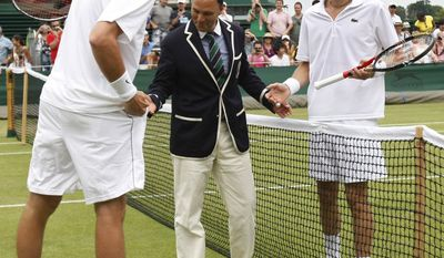 John Isner of the US, left, and Nicolas Mahut of France, right, talk with chair umpire Mohamed Lahyani before resuming their their epic men's singles match at the All England Lawn Tennis Championships at Wimbledon on Thursday, June 24, 2010. The match was resumed with the sores tied at 59 all in the fifth set. (AP Photo/Alastair Grant)