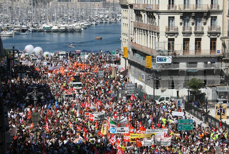 People march during a protest on the Old-Port in Marseille, southern France, on Thursday June 24, 2010. Many French trains stood still, schoolchildren played instead of studied and post offices were shuttered as workers nationwide went on strike Thursday to protest President Nicolas Sarkozy's plans to raise the retirement age to 62. Nearly 200 marches and protests are planned for several cities over a broad reform to the money-losing pension system, part of efforts around Europe to cut back on growing public debts. (AP Photo/Claude Paris)