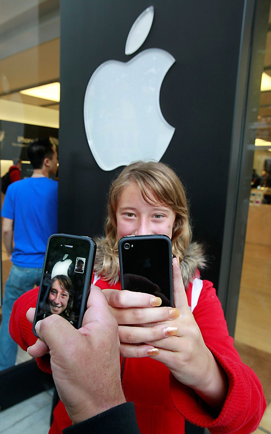 Emilie Weideman and her father, Marc Weideman, of Fremont, Calif., uses the new Apple iPhone 4 program FaceTime after purchasing the new device. (AP Photo/Paul Sakuma)
