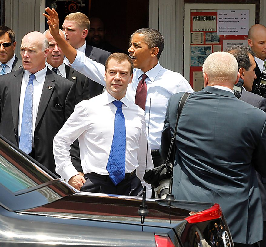 President Barack Obama, accompanied by Russian President Dmitry Medvedev, and others, waves as they leave Ray's Hell Burger in Arlington, Va., Thursday, June 24, 2010. (AP Photo/Charles Dharapak)