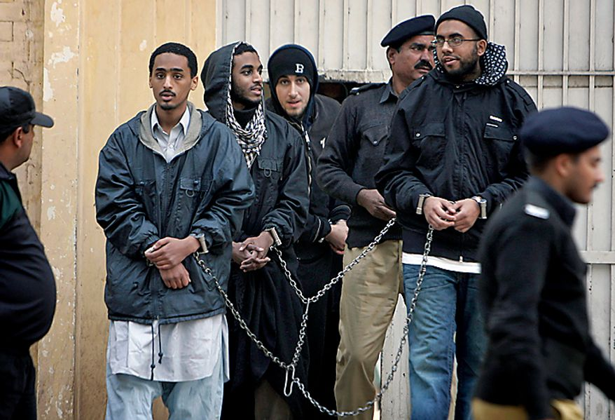 In a file photo, Pakistani police officers with detained American Muslims leave a police station to send them into prison in Sargodha, Pakistan, Monday, Jan. 4, 2010. The five American men were convicted Thursday on terror charges by a Pakistan court and sentenced to 15 years in prison each, a prosecutor said. (AP Photo/K.M. Chaudary)
