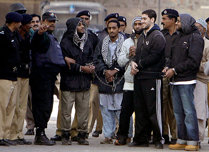 In a file photo, detained American Muslims, center, are escorted by Pakistan police officers as they leave after appear in an anti terrorist court in Sargodha, Pakistan, Monday, Jan. 4, 2010. The five American men were convicted Thursday on terror charges by a Pakistan court and sentenced to 15 years in prison each, a prosecutor said. (AP Photo/K.M. Chaudary)