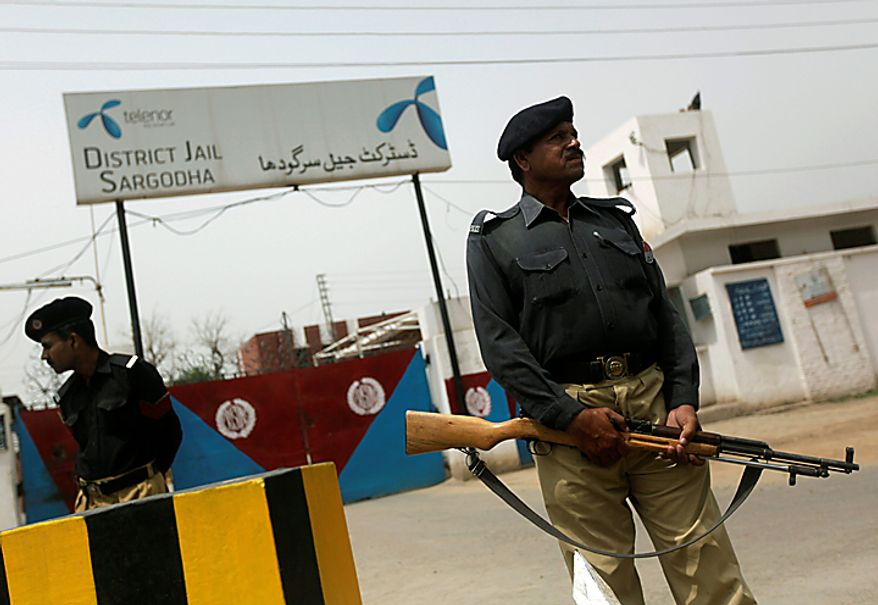 Pakistani police officers stand guard outside the district jail where five young Muslims from the Washington, D.C. area, who were arrested in Pakistan in December, are being held, in Sargodha, Pakistan, Thursday, June 24, 2010. The five American men were convicted Thursday on terror charges by a Pakistan court and sentenced to 15 years in prison each, a prosecutor said. The judge handed down two prison terms for each man, one for 10 years and the other for five, said deputy prosecutor Rana Bakhtiar.  (AP Photo/Dita Alangkara)