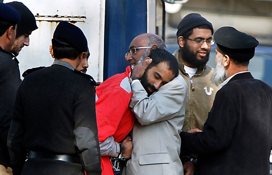 In a file photo, A detained American Muslim, center, is hugged by his father as another, second right, looks on upon their arrival to appear in an anti terrorist court in Sargodha, Pakistan, Tuesday, Feb. 16, 2010. The five American men were convicted Thursday on terror charges by a Pakistan court and sentenced to 15 years in prison each, a prosecutor said. The judge handed down two prison terms for each man, one for 10 years and the other for five, said deputy prosecutor Rana Bakhtiar. (AP Photo/Anjum Naveed)