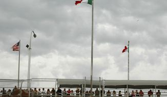 **FILE** In this June 7, 2010 photo, people stand on the Paso Del Norte border bridge to watch the police activity below after 15-year-old Sergio Adrian Hernandez Huereca was killed below the bridge in the city of Ciudad Juarez, Mexico. Federal records show that Hernandez was among El Paso's most wanted juvenile smugglers. (Associated Press)