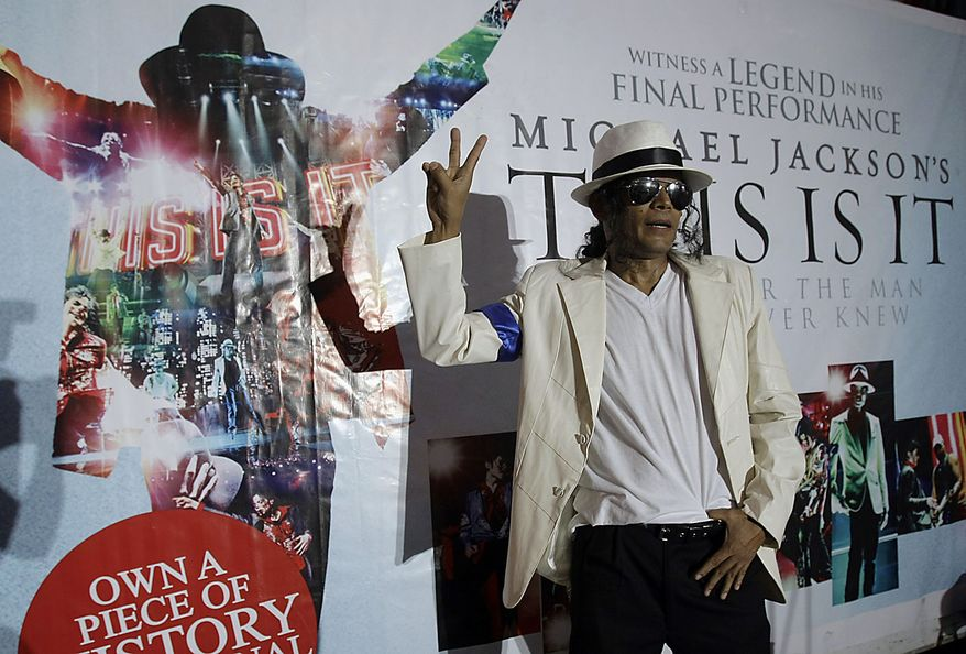 Michael Jackson impersonator Elmer Capistrano gestures after his performance commemorating the first death anniversary of the legendary king of pop music at a shopping mall in Manila, Philippines Friday, June 25, 2010. (AP Photo/Pat Roque)