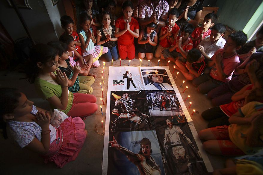 Michael Jackson's fans light candles around his posters on his first death anniversary in Jammu, India, Friday, June 25, 2010. (AP Photo/Channi Anand)