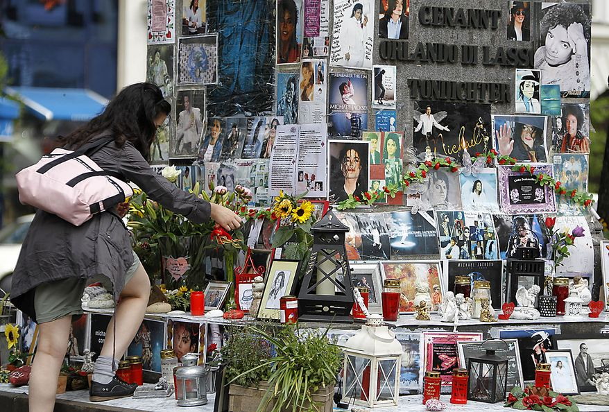 A woman places flowers at a memorial for Michael Jackson in Munich, southern Germany, on Thursday, June 24, 2010. German fans commemorated the first anniversary of the superstar's death. (AP Photo/Matthias Schrader)