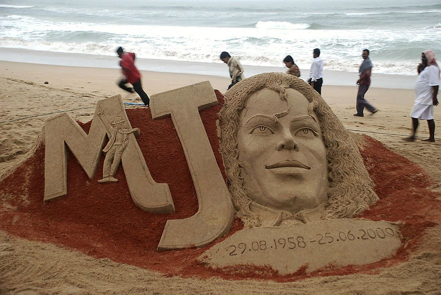 People walk past a sand sculpture of pop music icon Michael Jackson created to mark the first anniversary of his death, at the Bay of Bengal coast, in Puri, Orissa state, India, Thursday, June 24, 2010. (AP Photo)