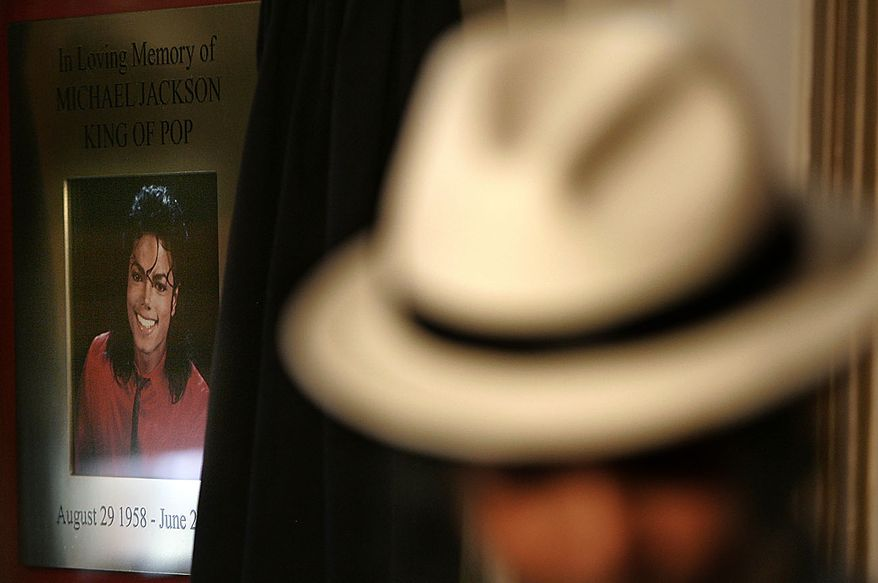 Ricko Baird, a performer from the 'Thriller Live' show poses in the foreground, in front of the commemorative plaque to mark the anniversary of the death of U.S. performer  Michael Jackson, as it is unveiled at the Lyric Theatre in London's West End, Thursday, June 24, 2010. After his death on June 25, 2009,  the Lyric Theatre has become a focus for fans who created a shrine of flowers, candles, and tributes as it is the home to the 'Thriller Live' show celebrating the music of Jackson and the Jackson 5. (AP Photo/Akira Suemori)