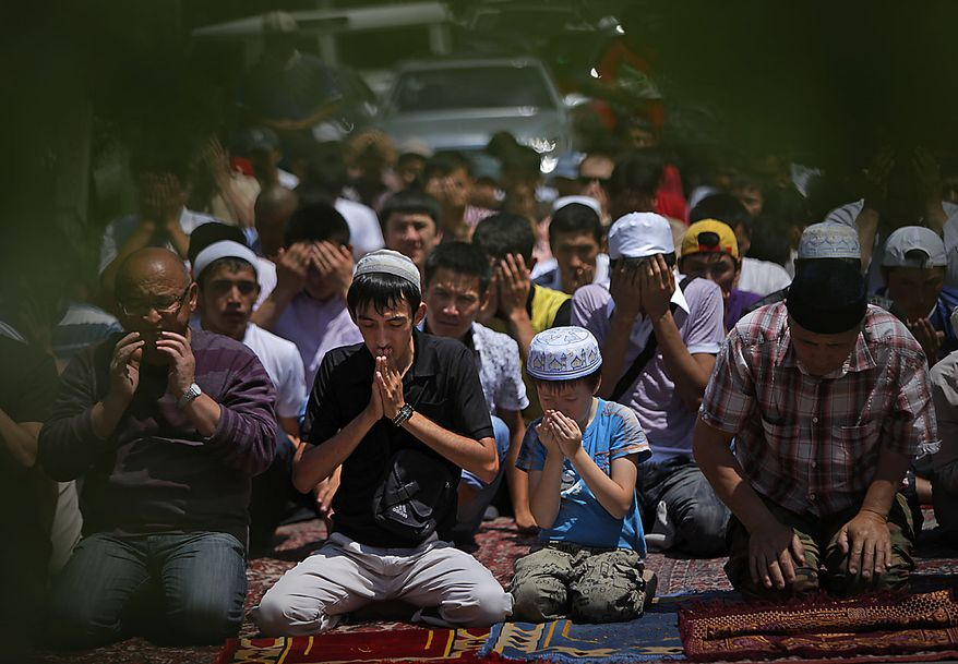 Ethnic Uzbek and Kyrgyz citizens pray together during a Friday prayer outside a mosque at Uzbek ethnic neighbourhood  in Bishkek, Kyrgyzstan, Friday, June 25, 2010. U.S. President Barack Obama said the two had also agreed to coordinate on humanitarian aid for Kyrgyzstan, wracked by turmoil in the wake of the president's ouster. Kyrgyzstan's president was driven from power in April amid corruption allegations, sparking violence that has left about 2,000 people dead and 400,000 ethnic Uzbeks homeless. (AP Photo/Alexander Zemlianichenko)