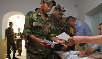 Kyrgyz soldiers receive their ballot papers at a polling station as early voting is held for Sunday's referendum in the southern Kyrgyz city of Osh, Kyrgyzstan, Friday, June 25, 2010. Kyrgyz authorities say they have arrested a nephew of deposed President Kurmanbek Bakiyev whom they accuse of playing a key role in organizing the ethnic rioting that killed hundreds of people. This month's unrest tore apart the Central Asian nation's south, with Kyrgyz rampaging through Uzbek neighborhoods. As many as 400,000 people fled their homes.(AP Photo/Sergei Grits)