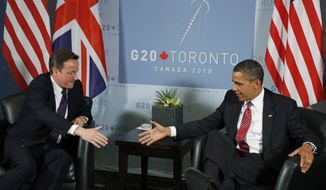 Britain's Prime Minister David Cameron, left, and U.S. President Barack Obama, right, reach out to shake hands during their bilateral meeting on the sidelines of the G-20 summit in Toronto, Saturday, June 26, 2010. (AP Photo/Lefteris Pitarakis)