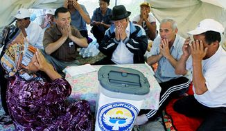 Ethnic Kyrgyz refugees and election commission officials pray after voting on a new constitution in Kyrgyzstan on Sunday. (Associated Press)