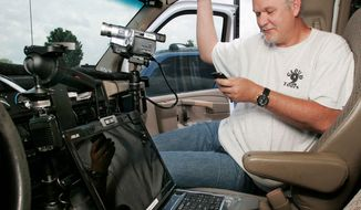 Storm chaser Charles Edwards, owner and operator of Cloud 9 Tours in Oklahoma, has a video camera mounted to the dashboard and a laptop computer to receive weather radar to help track tornadoes. (Associated Press)