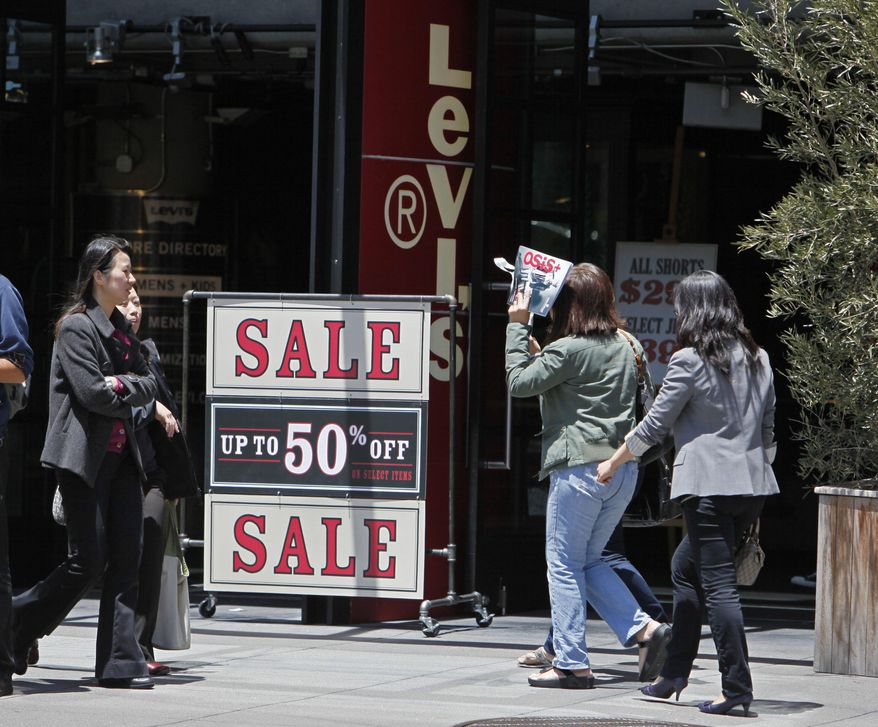 In this June 1, 2010, photo, people walk by a sale sign at the entrance of the Levi's store on Union Square in San Francisco. Retail sales plunged in May by the largest amount in eight months as consumers slashed spending on everything from cars to clothing. (AP Photo/Eric Risberg)