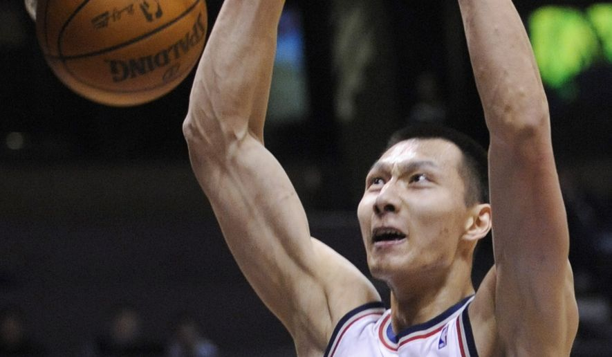 ASSOCIATED PRESS FILE - This Feb. 23, 2010, file photo shows New Jersey Nets' Yi Jianlian, of China, dunking during the first quarter of an NBA basketball game against the Portland Trail Blazers, in East Rutherford, N.J. Two people familiar with the deal tell The Associated Press the New Jersey Nets have traded forward Yi Jianlian to the Washington Wizards, creating even more room as they head into free agency.