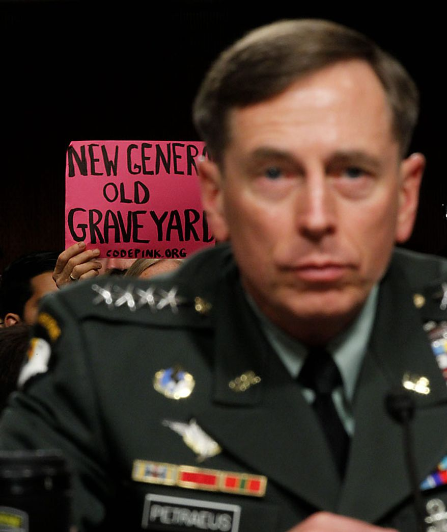 A protester holds a sign on Capitol Hill in Washington, Tuesday, June 29, 2010, as Gen. David Petraeus testifies before the Senate Armed Services Committee hearing to be confirmed as President Obama's choice to take control of forces in Afghanistan .(AP Photo/Pablo Martinez Monsivais)